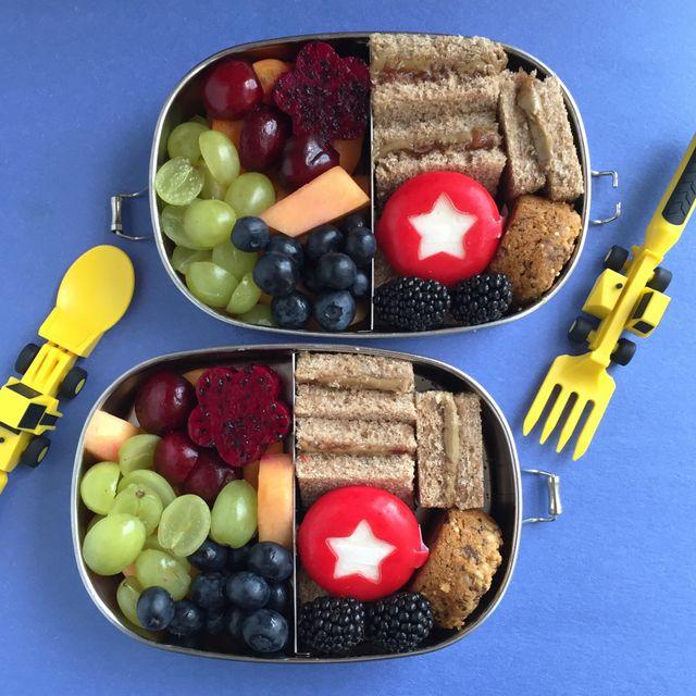 Due contenitori per il pranzo divisi in acciaio inossidabile con panini, frutti di bosco, uva, ciliegie, melone e una piccola forma di formaggio con una stella ritagliata dal guscio di cera rossa.