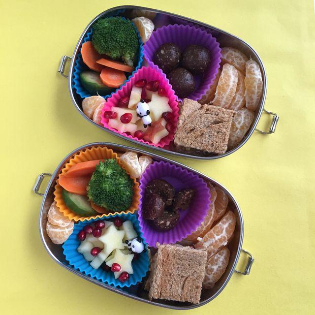 due contenitori per il pranzo aperti in acciaio inossidabile con pirottini in silicone come divisori.  Piccoli quadrati di arenaria, clementine, stelle di mele, melograni, broccoli e carote e palline energetiche datate