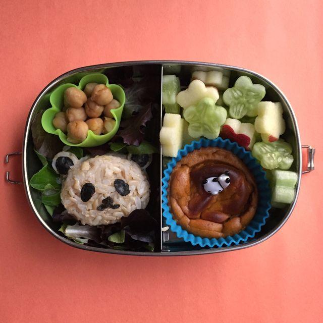 un lunch box condiviso con stelle di mele e cetrioli, un muffin, una pirofila in silicone a forma di fiore farcita con ceci e un riso integrale a forma di panda.