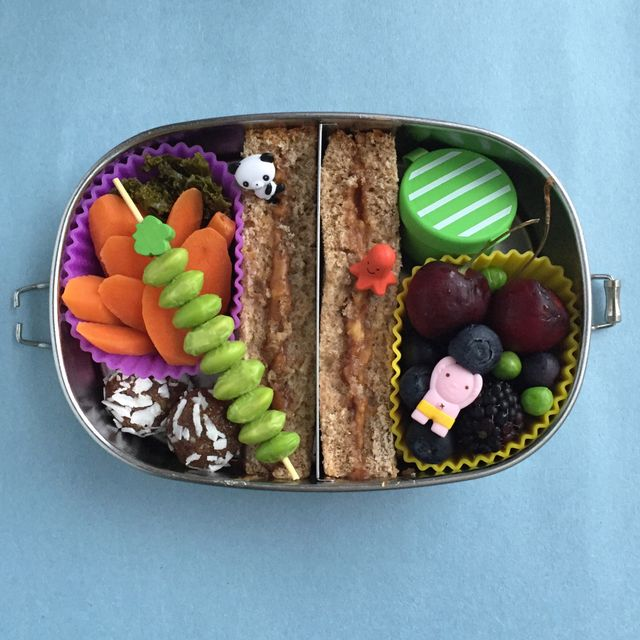 Lunch box in acciaio inox diviso con due metà di sabbia, frutti di bosco misti e ciliegie, cogli denti lunghi con edamame inclinato, carote e palline energetiche datate.
