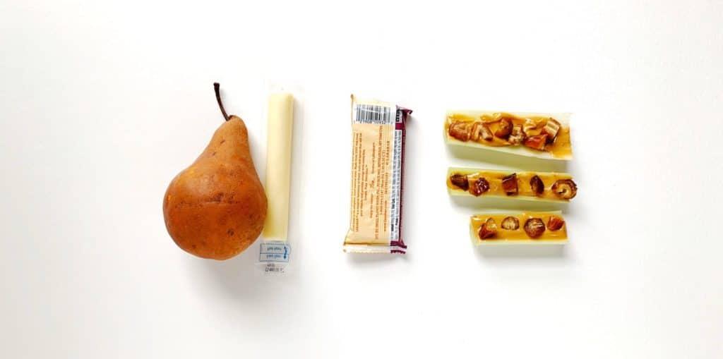 L'immagine di un'idea per il pranzo usa e getta composta da una pera, un bastoncino di formaggio, una barretta di cereali e bastoncini di sedano ripieni di burro di arachidi, conditi con uvetta.