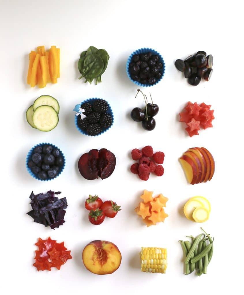 Porzioni di frutta e verdura estiva delle dimensioni di uno spuntino per un pranzo usa e getta disposto in una griglia.  Carote, spinaci, frutti di bosco, uva, zucchine, pesche, cavoli, tutolo di mais, meloni, fagiolini e ciliegie.
