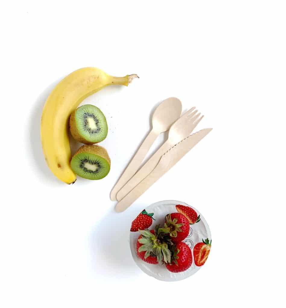 Immagine di un'idea per il pranzo usa e getta composta da una banana, kiwi, una tazza di yogurt con fragole fresche in cima e utensili da cucina riciclabili