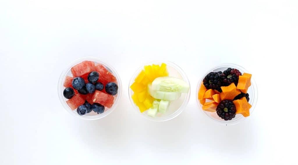 Tre tazze di frutta e verdura fatte in casa con un pranzo usa e getta.  Anguria e mirtilli sono uno di questi.  Il prossimo è mango e cetriolo.  Il terzo ha carote e more a forma di stella,