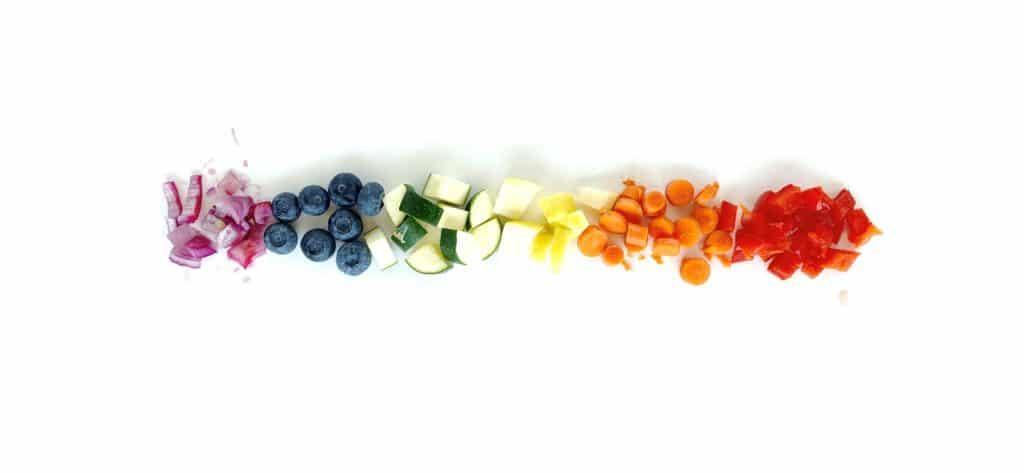 un arcobaleno di frutta e verdura tritate in quantità adeguate a ciò che mangiano i bambini di tre anni