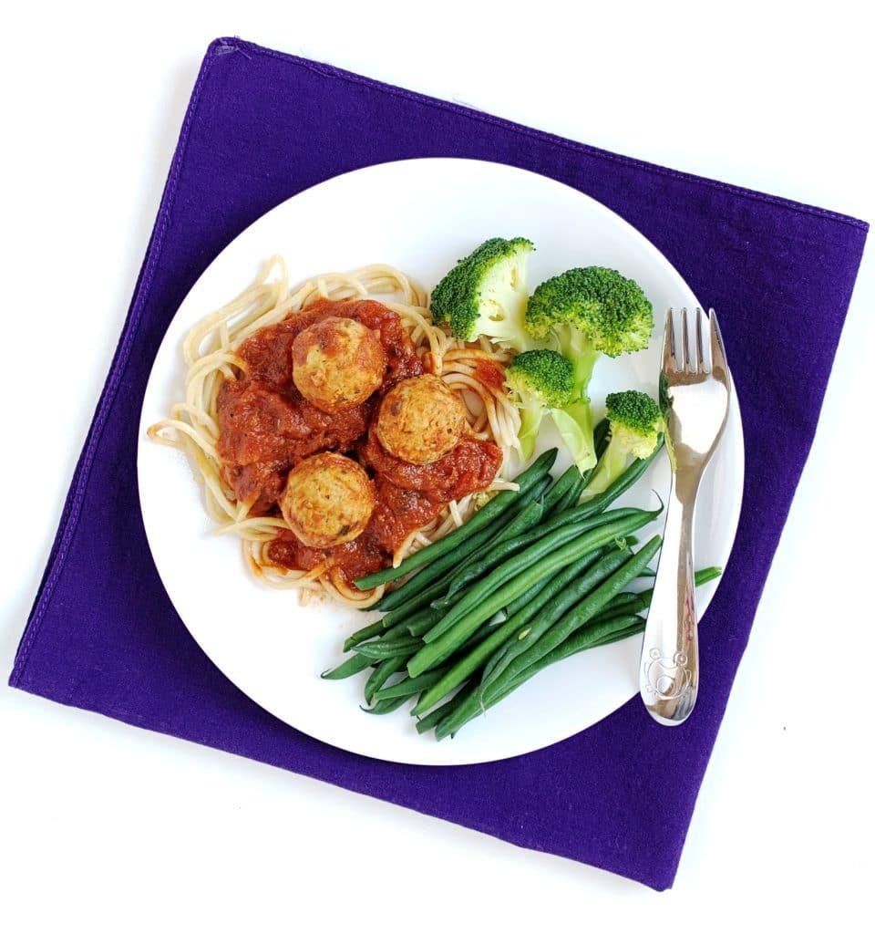 Un'immagine di ciò che un bambino esigente dovrebbe portare a cena: un piatto di spaghetti, salsa, broccoli, fagiolini e polpette.