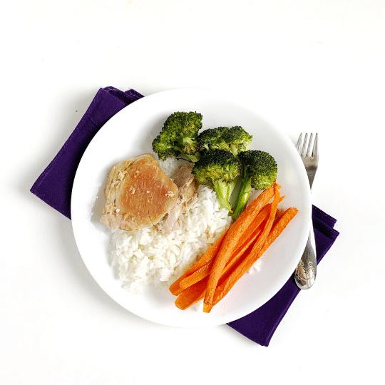 Un pasto compatto nutriente con cosce di pollo, broccoli, carote e riso.