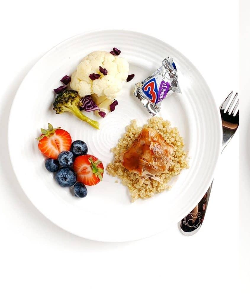 Immagine di un piatto con pollo, quinoa, verdure, frutta e un piccolo pezzo di caramella