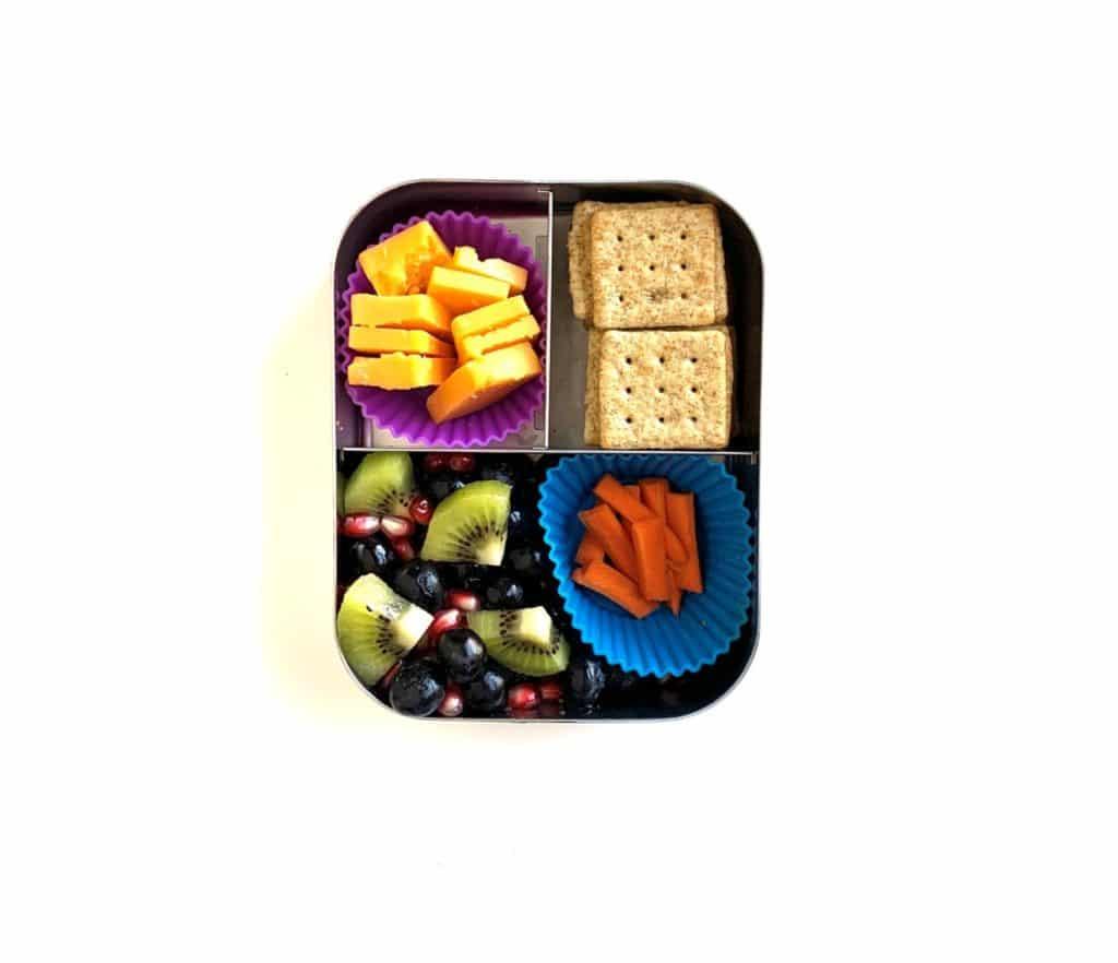 idea lunchbox su cosa mangiano i bambini di tre anni: carote, kiwi, frutti di bosco, fette di formaggio e panini con cracker PB