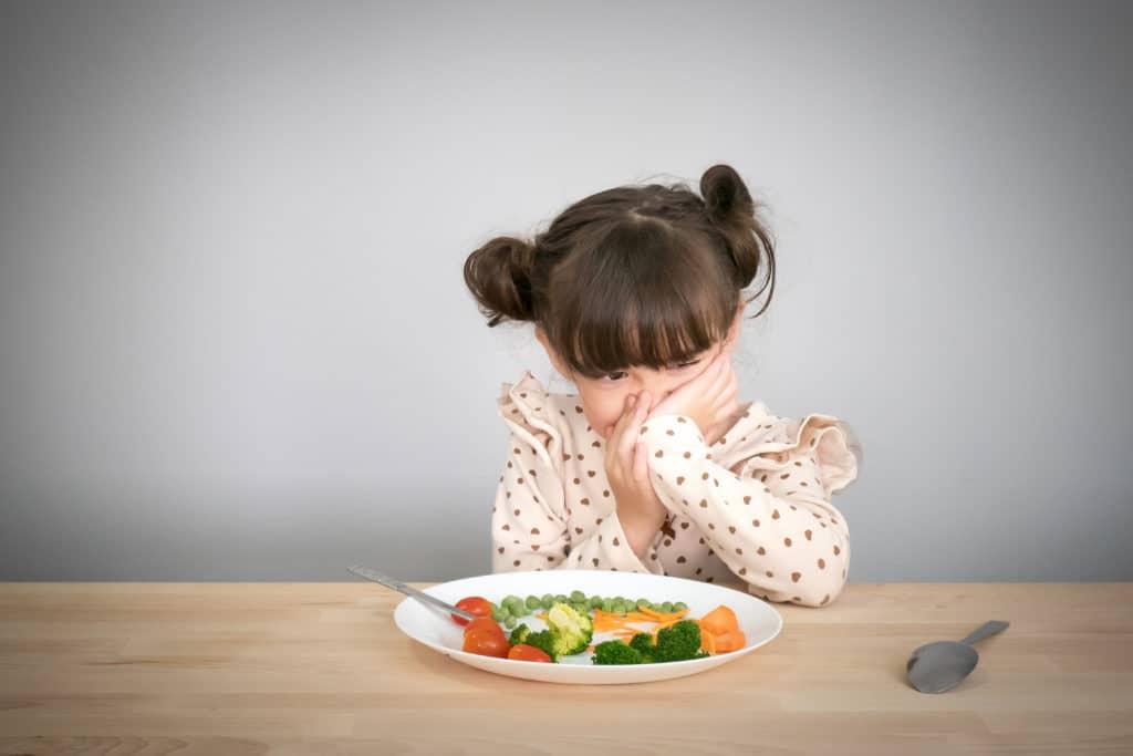 Bambino insoddisfatto al pasto dei genitori che chiede al bambino di non consumare cibo