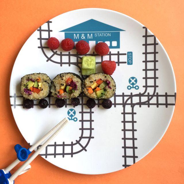 piatto bianco con binari ferroviari e nome personalizzato stazione ferroviaria con treno di sushi vegetale con ruote di bacche