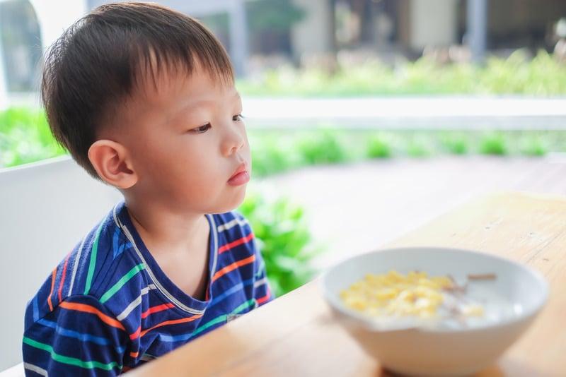 Ragazzo schizzinoso di 2 anni che fissa il cibo che non mangia
