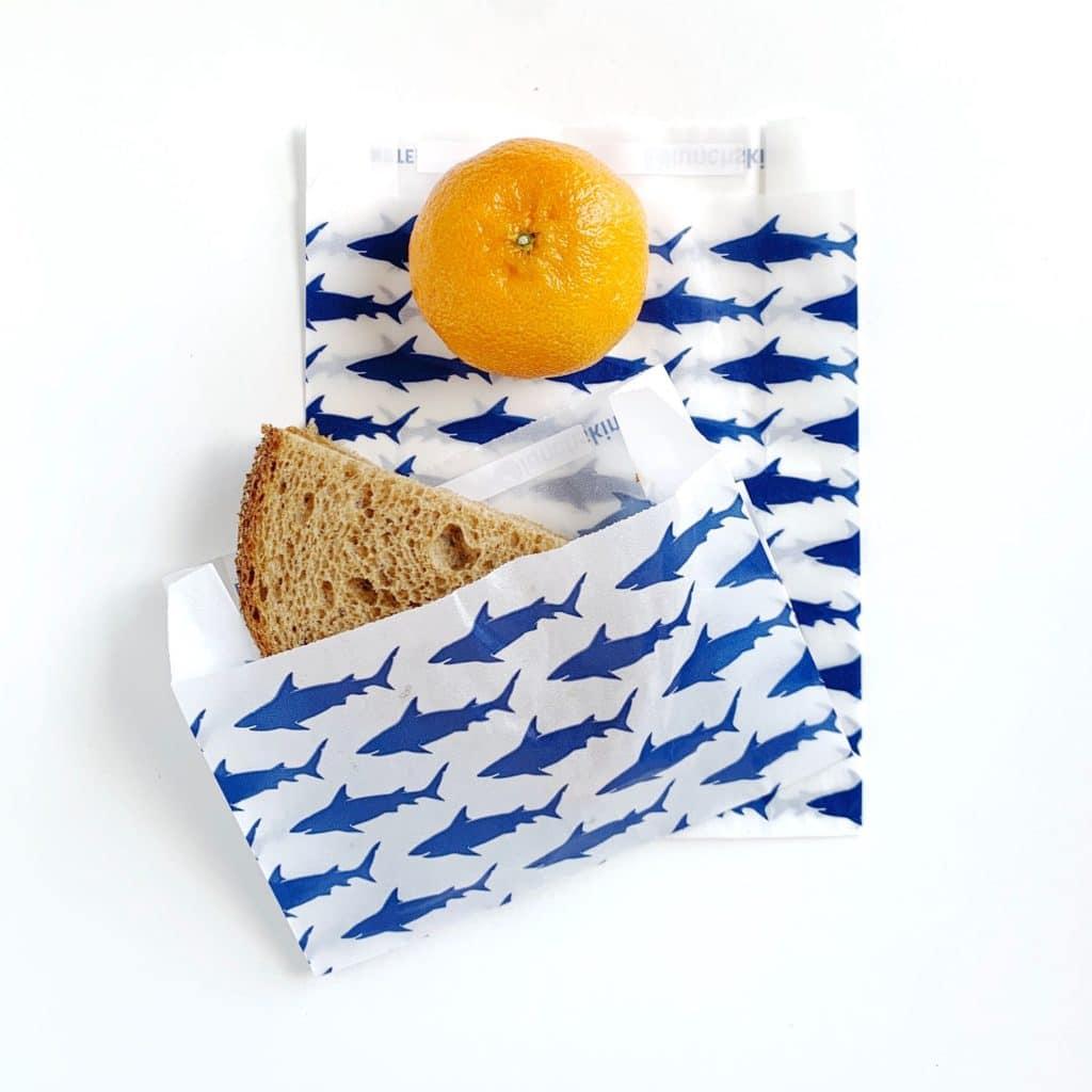 Immagine di un sacchetto per il pranzo usa e getta per panini in carta bianca con squali blu su di esso.  Dentro c'è un panino e accanto una clementina.